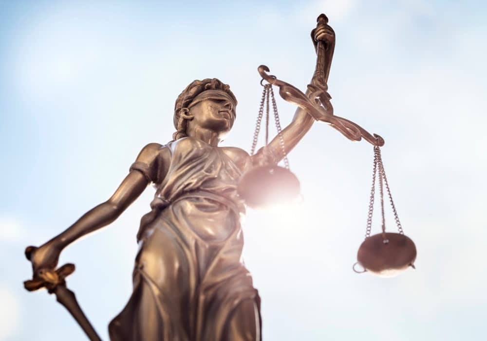 Legal law concept statue of Lady Justice with scales of justice sky background stock phot