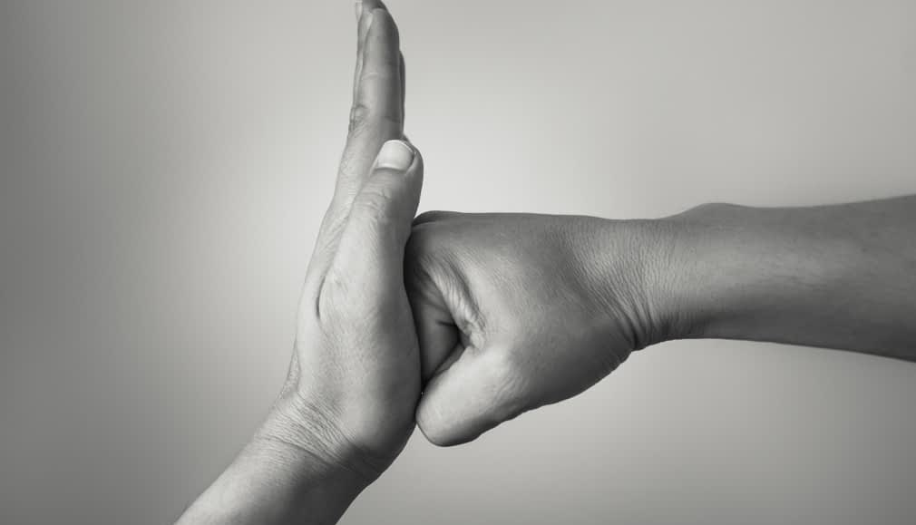 """Black and white photo of person punching, other hand is up in """"stop"""" signal"""